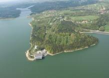 Ujęcie zakładu z lotu ptaka. Widać budynki, las oraz zbiornik Dobczycki.